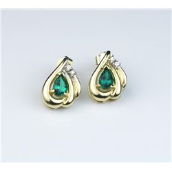 Stylish earrings with matching Chatham  created emerald and fine side diamonds in 14  karat yellow g