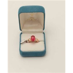 One 18k rose gold ladies ring set with a  Burmese ruby cabochon weighing approx 5 ct   and 2 side di