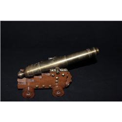 "Desk size brass signal cannon on wood  carriage, approximately 11"" overall and 6""  wide; good condit"