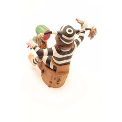 Wood carving of a Kachina Jester seated on a  log eating watermelon.  The base of the piece  is mark