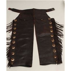 """Fringed and concho mounted chaps marked """"R.T.  Frazier, Pueblo, Colorado"""". Shows tears and  aging. I"""