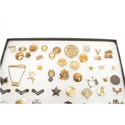 Lot of U.S. military medals and insignias in  large riker case.       Est.:  $50-100