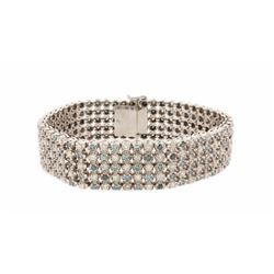 BRACELET: 10kt white gold diamond bracelet set with white and treated blue round brilliant cut diamo