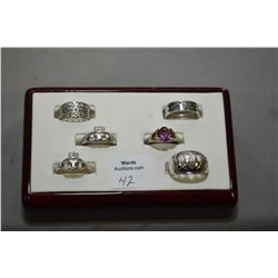 Six sterling silver rings including two Claddagh rings