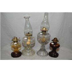Four vintage oil lamps including a pair of amber glass and two colourless lamps with chimneys