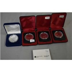 Four boxed coins including three 1978 Commonwealth games and a pure silver 1 oz. 1994 Canadian Maple
