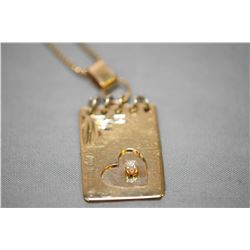 "Ladies 14kt yellow gold note book motif pendant set with small diamond on a 10kt yellow gold 24"" nec"