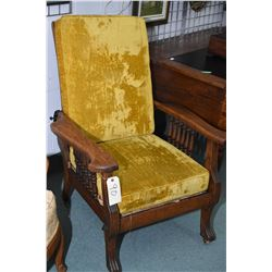 Antique oak Morris chair with turned spindles, claw feet and upholstered cushions