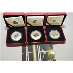 Three Royal Canadian mint glow in the dark 25 cent coins from the Pre-historic Creatures series incl