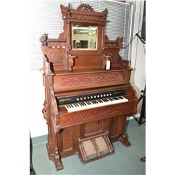 Antique Canadiana pump organ with fretwork and turned decoration, candle holders and bevelled mirror