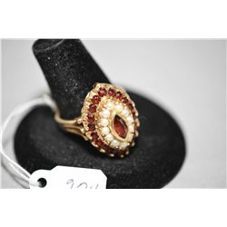 Ladies 14kt yellow gold ring wth marquise shaped cluster containing 1.44ct of Alamandite garnets and