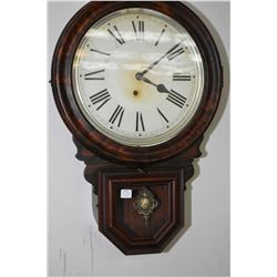 Antique wall mount wooden cased wall clock made by The E. Ingraham Co. with decorative visible pendu