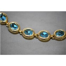 Ladies 14kt yellow gold bracelet, with 16.80ct of oval faceted and bezel set blue topaz gemstones. R