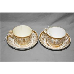 Pair of antique Minton bone china cups and saucers. Decorated with gilt borders, scrolls, stylized f