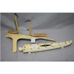 """Inuit handcarved and handpainted bone cribbage board with cribbage pieces, 11 1/2"""" in length, and tw"""