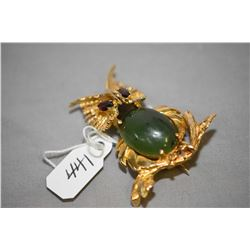 14kt yellow gold owl design brooch with garnet gemstone set and oval cabachon nephrite jade. Retail