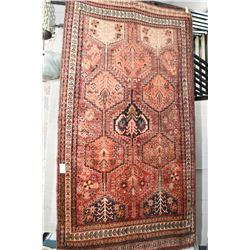 100% wool area rug with center medallion with geometric panels, multiple border shades of red with b