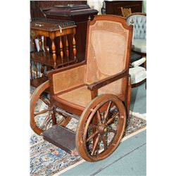French made antique wooden wheel chair with woven rattan back and seat, flip over foot support, pull