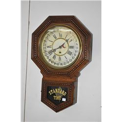Antique oak cased wall clock made by Wm. L. Gilbert Clock Co. with calendar and decorative visible p