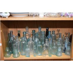 Shelf lot of vintage and antique glass bottles including apothecary, coloured bottles, clay ink jug,