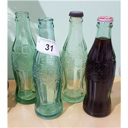 FOUR VINTAGE COCA-COLA BOTTLES