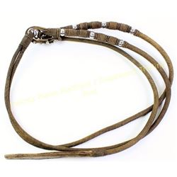 Finely braided rawhide reins with large leather popper.  Est. 75-175
