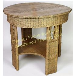 "Wicker and oak round parlor table 33"" round top with lower shelf.  Est. 50-100"