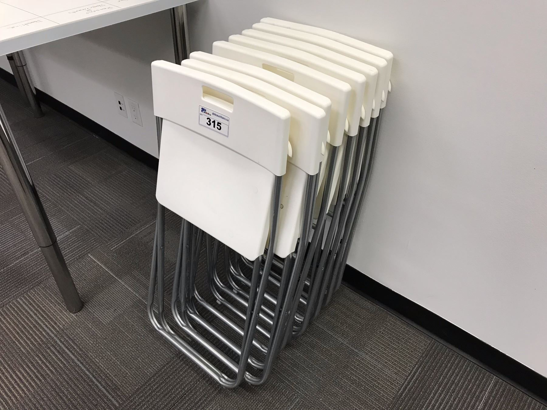 STACK OF 8 WHITE PLASTIC FOLDING CHAIRS