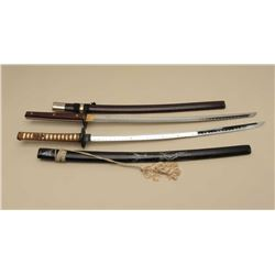 Two replica Japanese swords with scabbards; one scabbard is damaged.