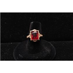 Unidentified orange-red cut stone in antique gold unmarked mount. 10-18k.