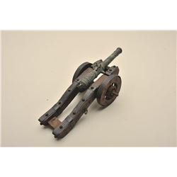 Ornate desk size decorator cannon with ornate  cast barrel on metal banded wood carriage.  Measures