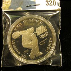 1983 S U.S. Olympics Proof Silver Dollar, Discus thrower, encapsulated.