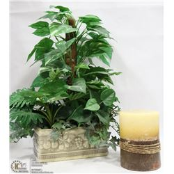 SILK PLANT AND LARGE CANDLE.