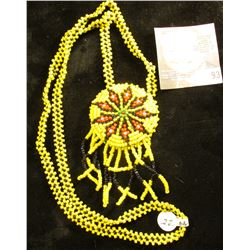 Necklace with pendant made from yellow, black, and red seed beads. 'Doc' valued it at $22.00.