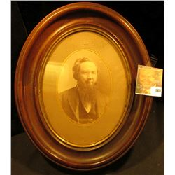"11 1/2"" Oval Wooden frame with gold trim and glass. Depicts photo of early 1800 era Pioneer with lon"
