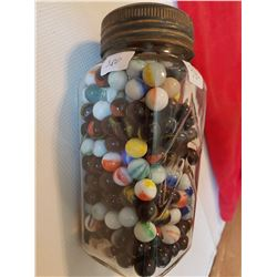 big jar of rare marbles in blue ribbon coffee jar
