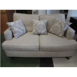 Beige loveseat with pillows