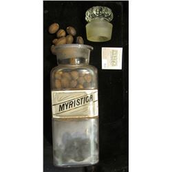 "Large 10"" x 3 1/4 Apothcary Jar with glass Stopper, some contents included.  Labeled ""Myristica"".  A"