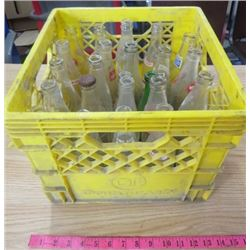 LOT OF 24 POP BOTTLES WITH YELLOW PLASTIC CRATE (VARIOUS BRANDS)