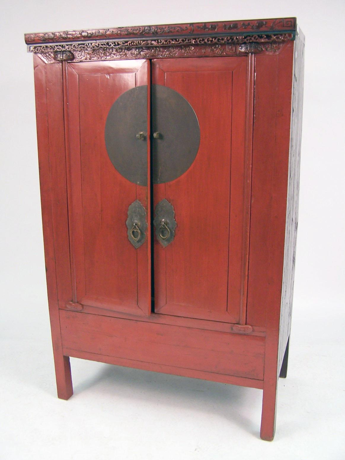 A CHINESE RED AND BLACK LACQUER CARVED HARDWOOD WEDDING CABINET