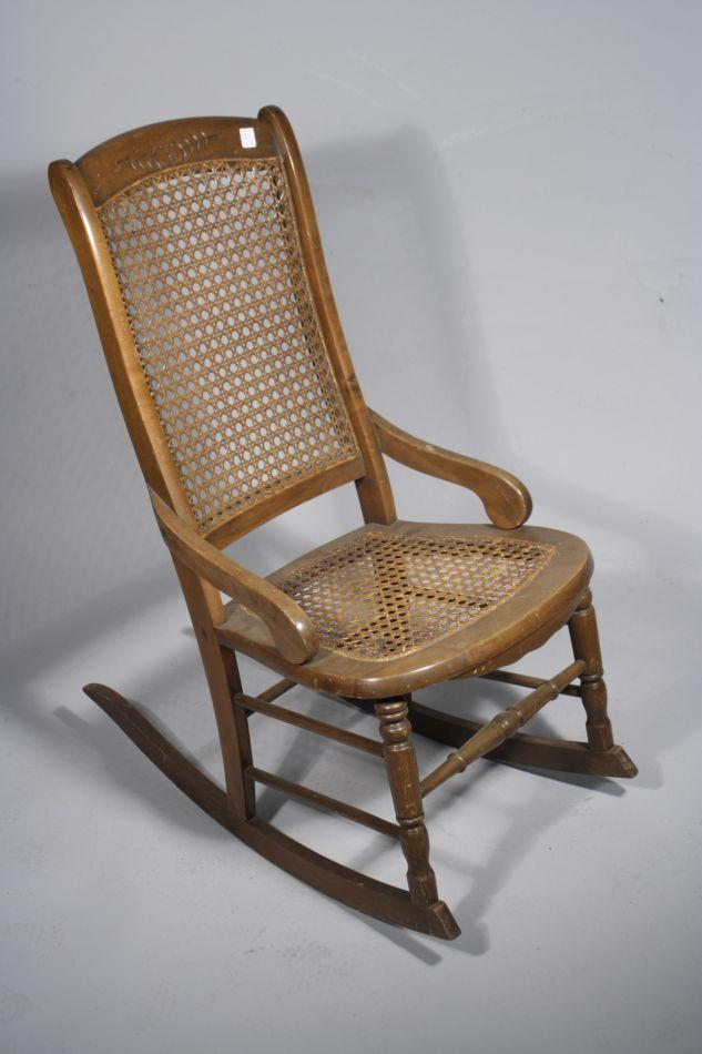 A victorian style pine rocking chair with caned seat