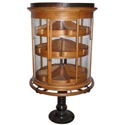 Candy display case, large round revolving oak floor case w/curved glass panels, cast iron base, unus