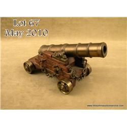 Small model of a brass deck cannon on wood  carriage with brass wheels in overall very good  conditi