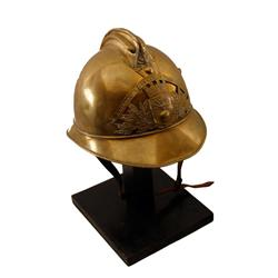 19th Century Brass Sappers Helmet of French origin on display stand showing fancy plate and motifs.