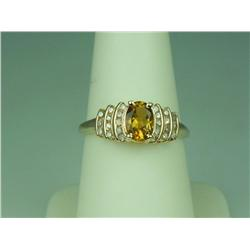 Pleasant 10K Yellow Gold Ladies Ring Set with a center oval citrine and channel set with 24 round cu