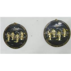 Pair round ebonized wall hangs with figures